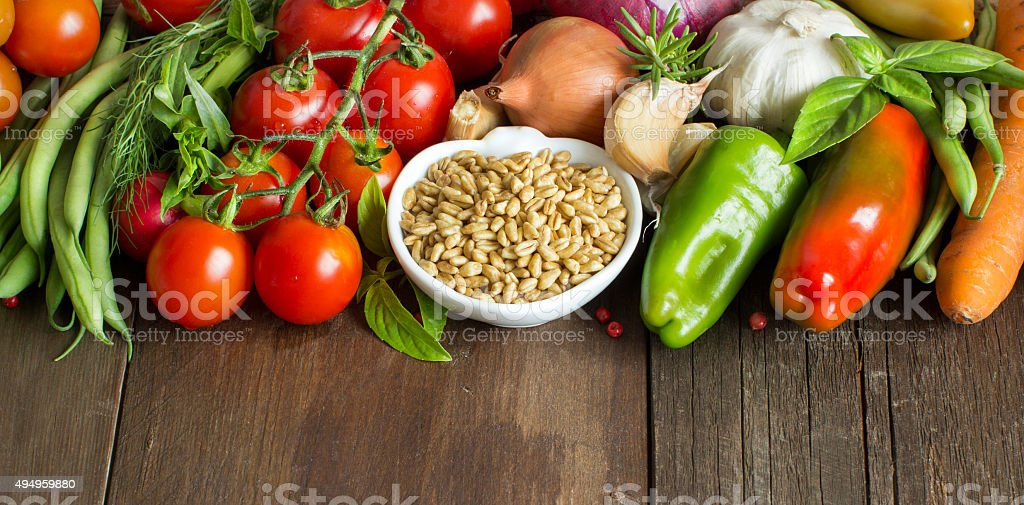 Spelt in a bowl and fresh vegetables stock photo