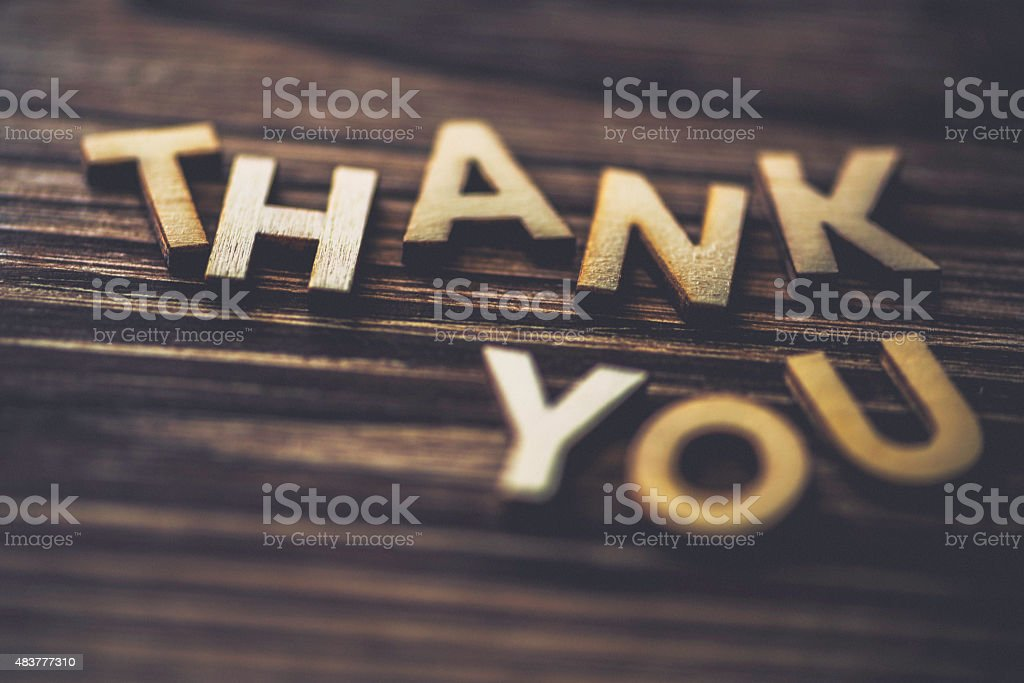 THANK YOU spelt out on wooden background stock photo