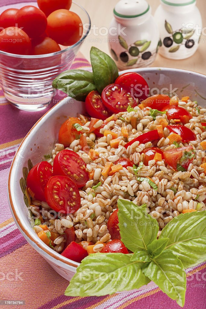 Spelt salad with tomatoes, carrots and basil royalty-free stock photo