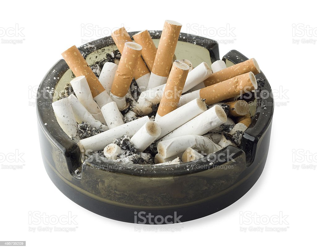 Spent cigarette butts and ash in a glass ashtray royalty-free stock photo