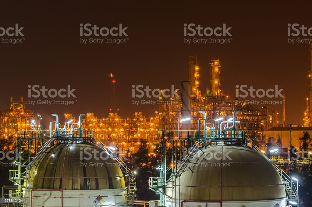 sphere gas tank with petrochemical plant background at night stock photo