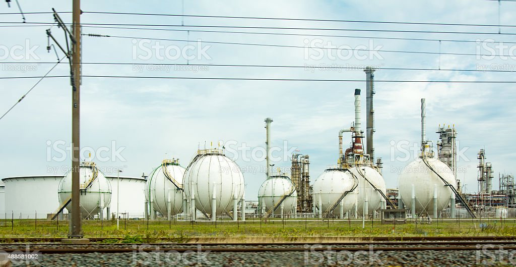 Spherical gas tanks behind train track stock photo