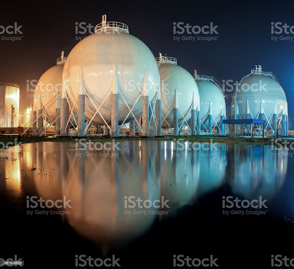 Spherical industrial storage tanks by waterside at night stock photo