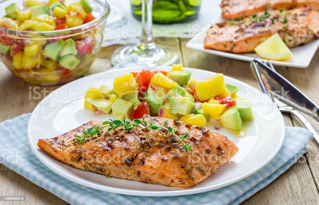 Spice grilled salmon with mango-avocado salsa on a white plate stock photo