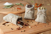 spice in linen sacks on wooden board at rustic style