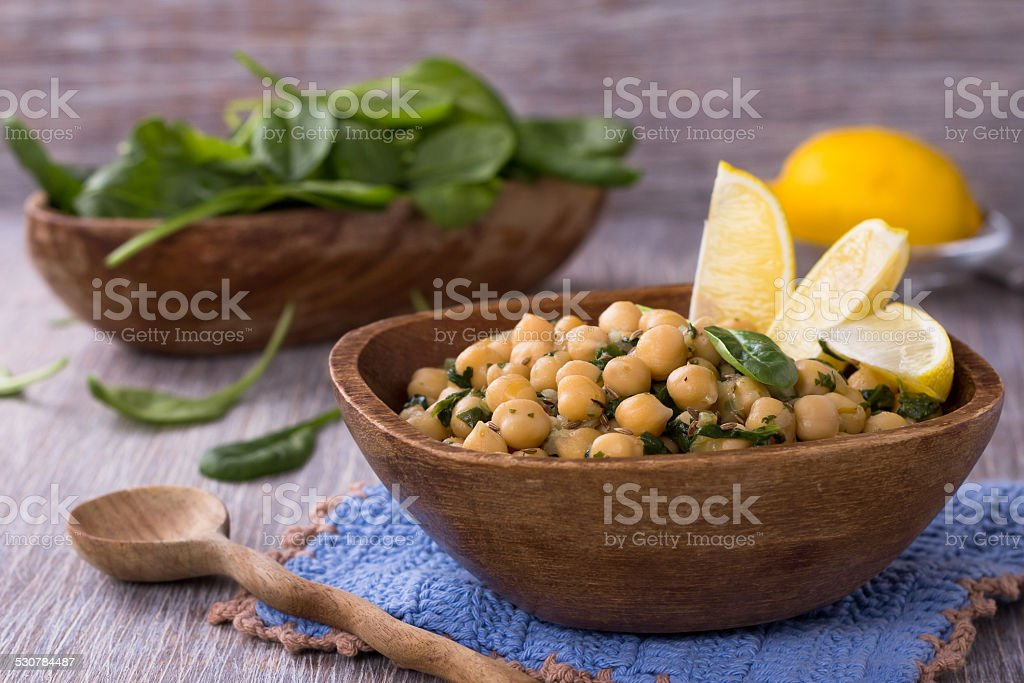 Spiced chickpeas with spinach in a wooden bowl stock photo