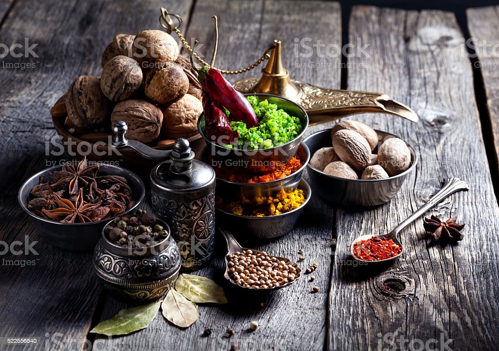 Spices and nuts at wooden table stock photo