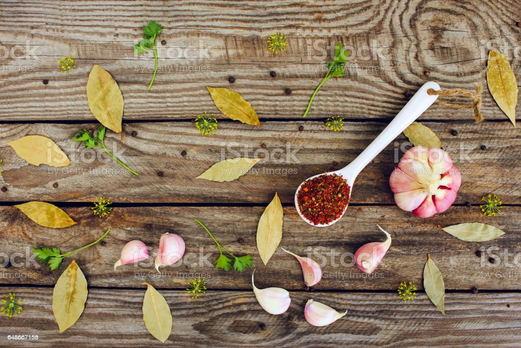 Spices, bay leaf, black pepper, garlic and dill on old wooden background. Top view stock photo
