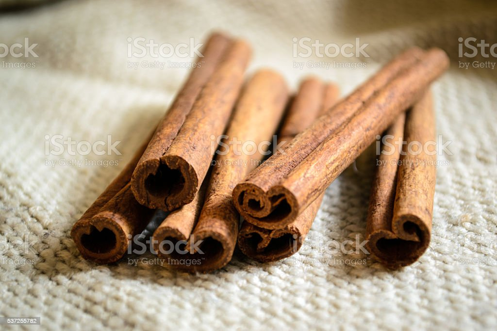 Spices cinnamon sticks on the cloth on a wooden table stock photo