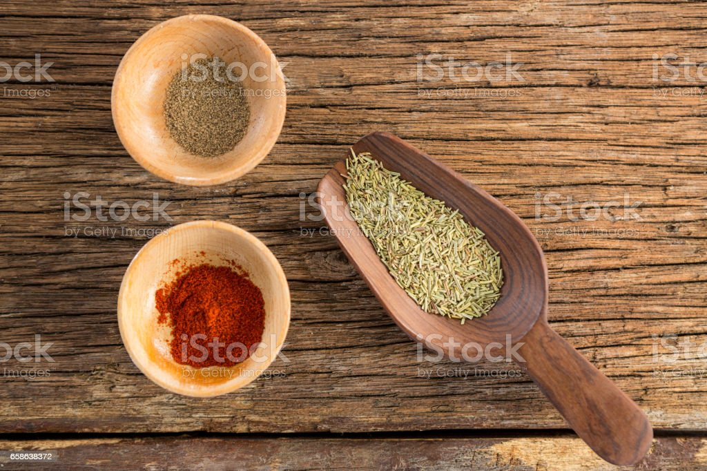 Spices in bowl and wooden spoon stock photo