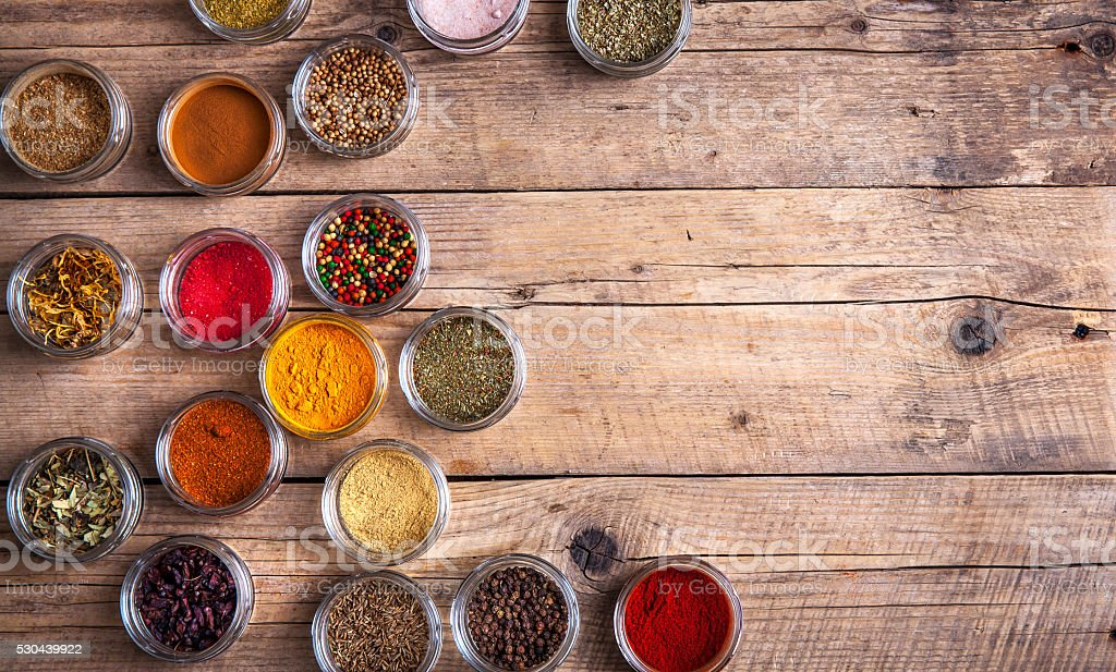 Spices in jars on wooden background. Food stock photo