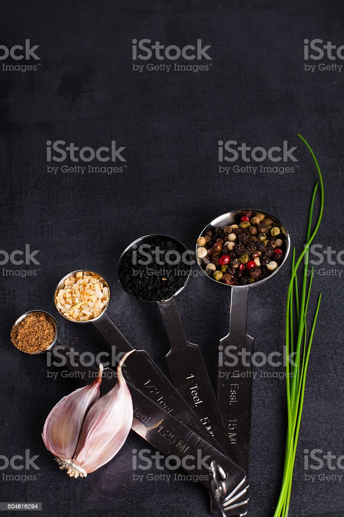 Spices in stainless steel measuring spoons, fresh herbs. Copy space. stock photo