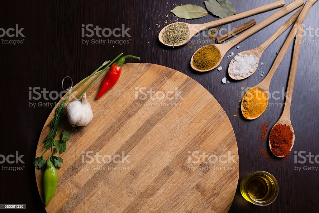 Spices in wooden spoons and empty round cutting board stock photo