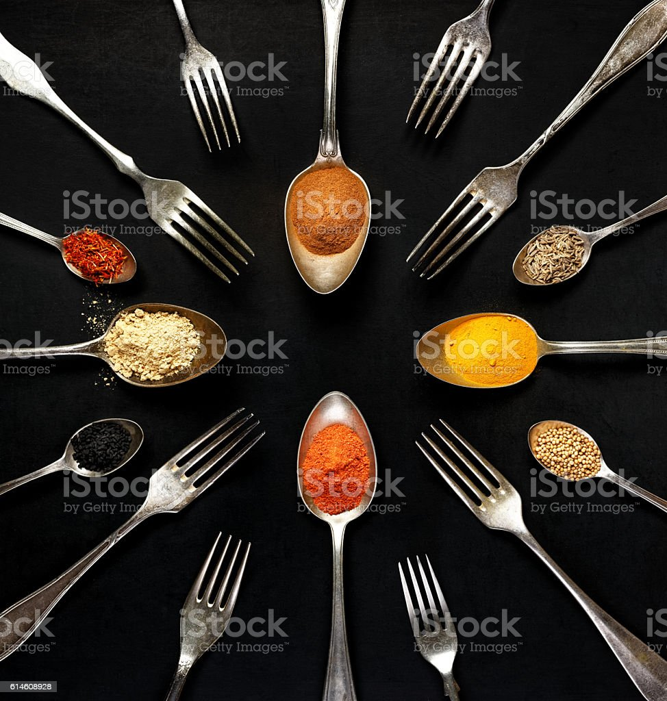 Spices on spoons on black background, top view stock photo