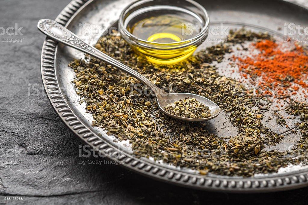 Spices, paprika, spoon, oil, tin plate on a black slate stock photo
