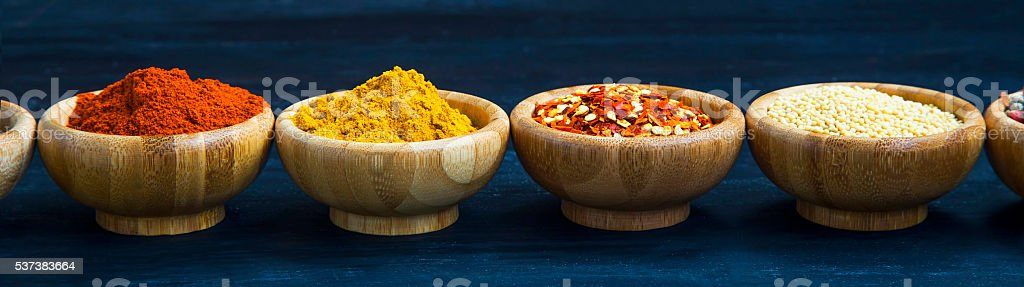 Spices powders and seeds in bamboo bowls stock photo