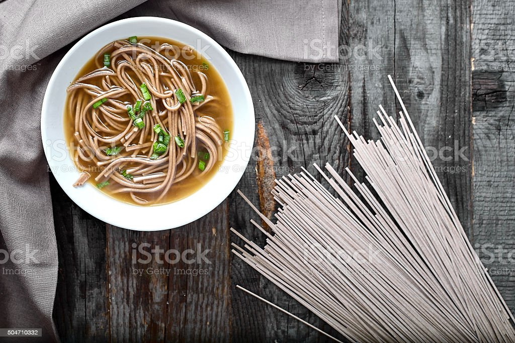 Spicy asian soup with soba noodles stock photo