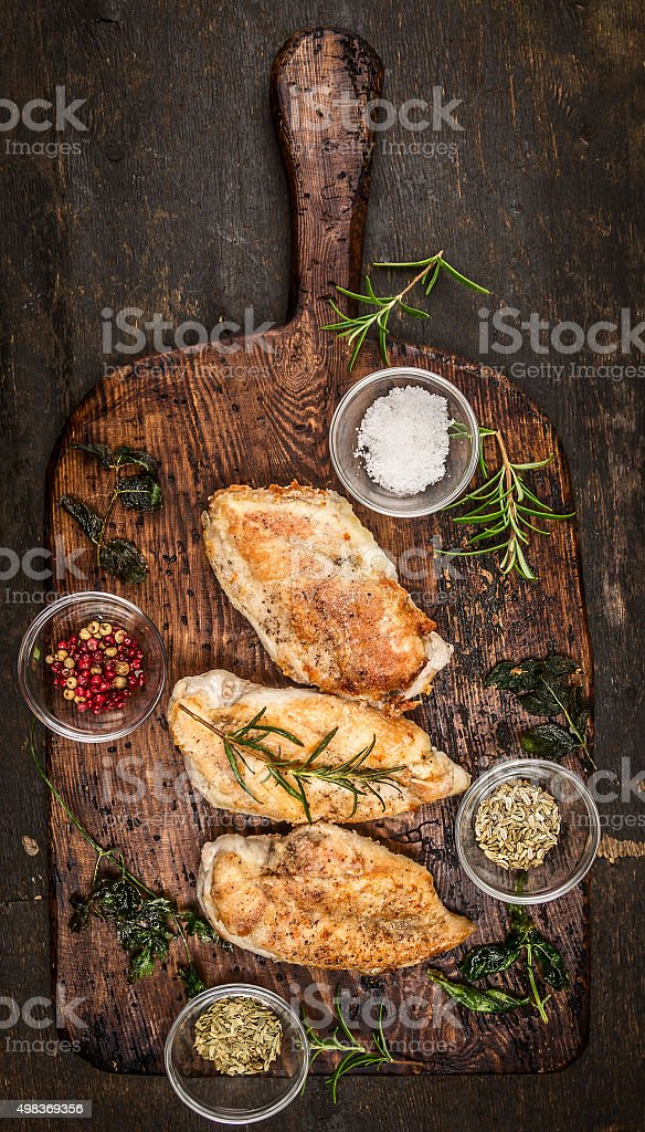 Spicy baked chicken breast on rustic wooden gutting board, stock photo