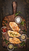 Spicy baked chicken breast on rustic wooden gutting board,