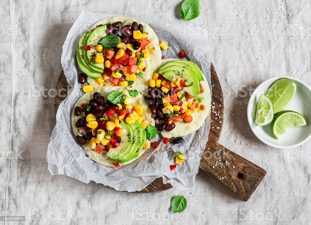 Spicy bean tortillas with corn salsa and avocado stock photo