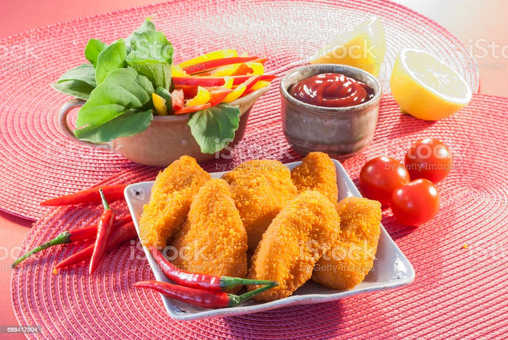 Spicy Breaded chicken fillets with red chilly lemon and cherry tomatoes with ketchup and bell pepper salads stock photo