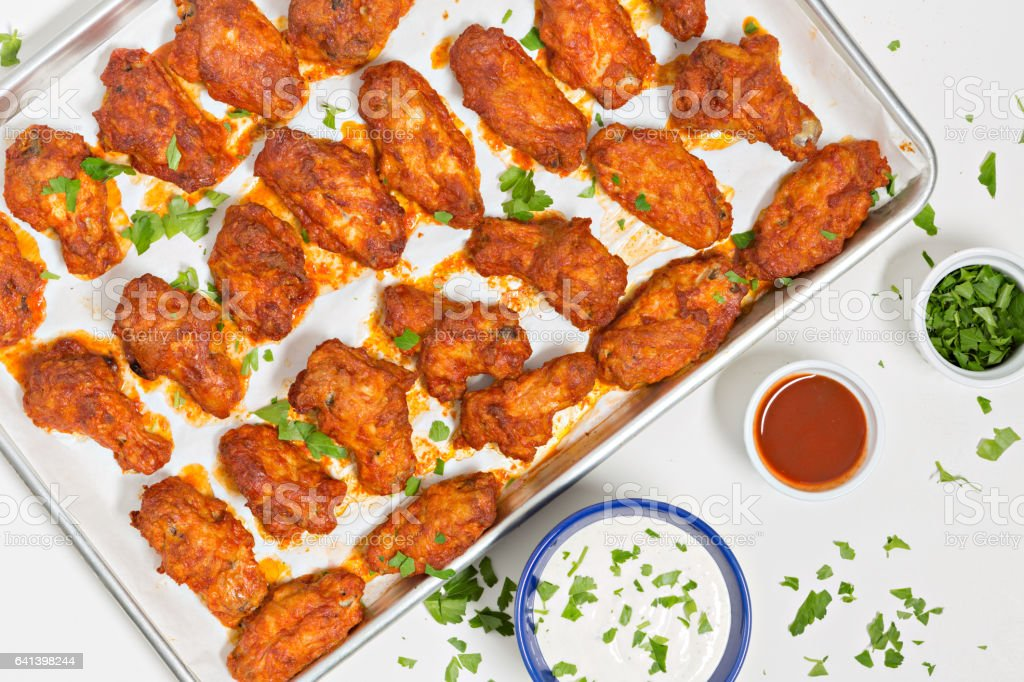 Spicy Buffalo Wings On A Baking Tray And Dipping Sauces stock photo