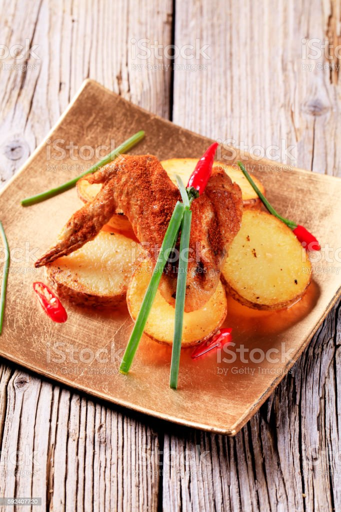 Spicy chicken wing and potatoes stock photo