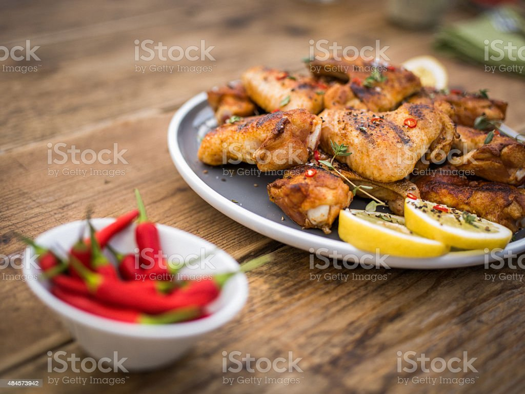 Spicy chicken wings with a bowl of red chillie peppers stock photo