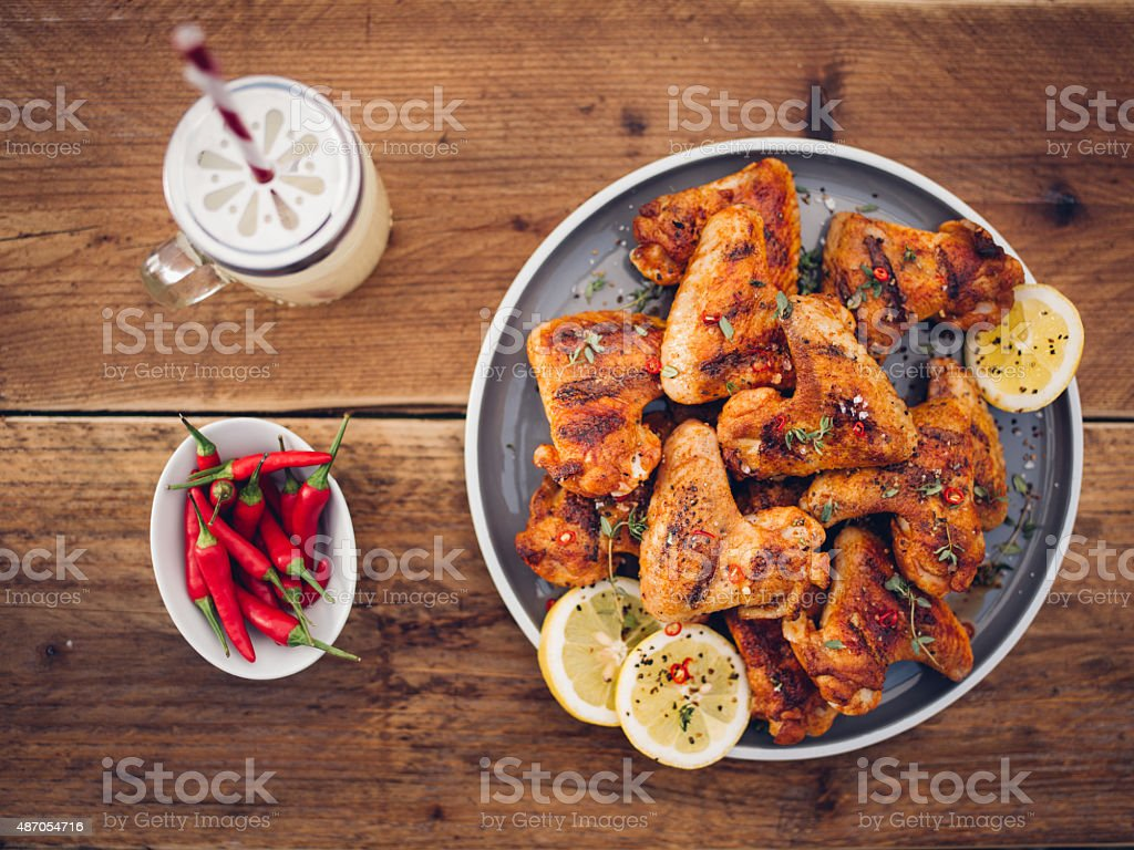 Spicy chicken wings with chillies and a summer drink stock photo