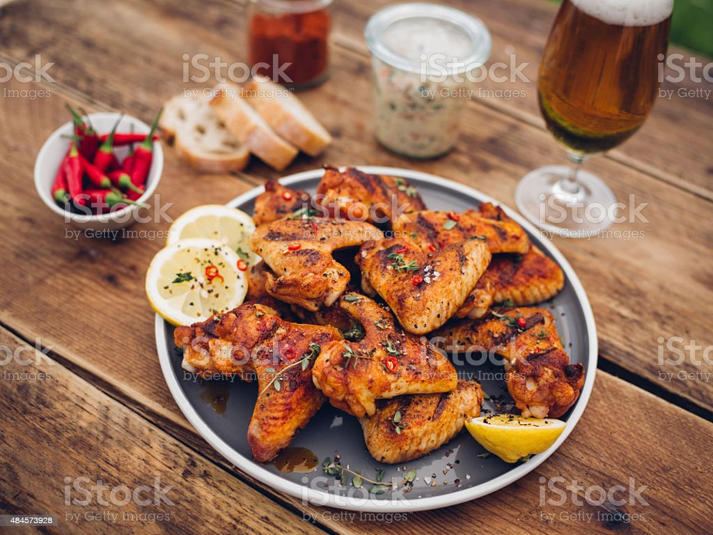 Spicy chicken wings with condiments and a glass of beer stock photo