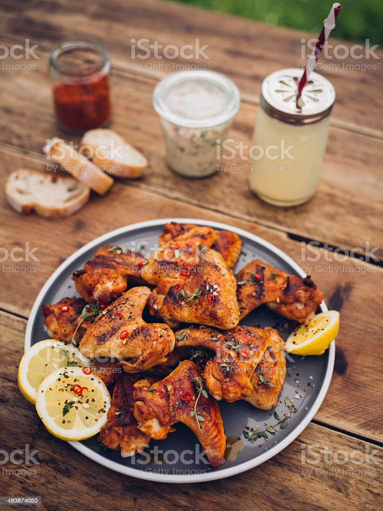 Spicy chicken wings with summer beverage and condiments stock photo