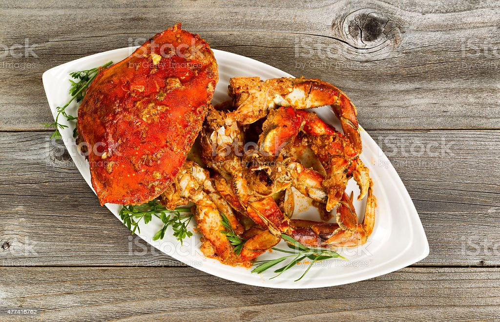 Spicy cooked crab on white plate with rustic wood stock photo