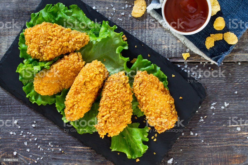 Spicy Fried Breaded chicken wings and fresh lettuce on a wooden table. stock photo
