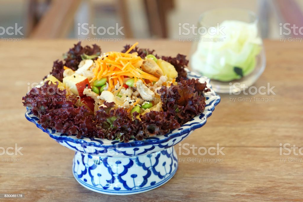 Spicy fruit salad mixed with pomelo, pineapple, cashew nuts, green bean (edamame) decorated with carrot and sesame seeds - Veganism Food is the practice of abstaining from the use of animal products. stock photo