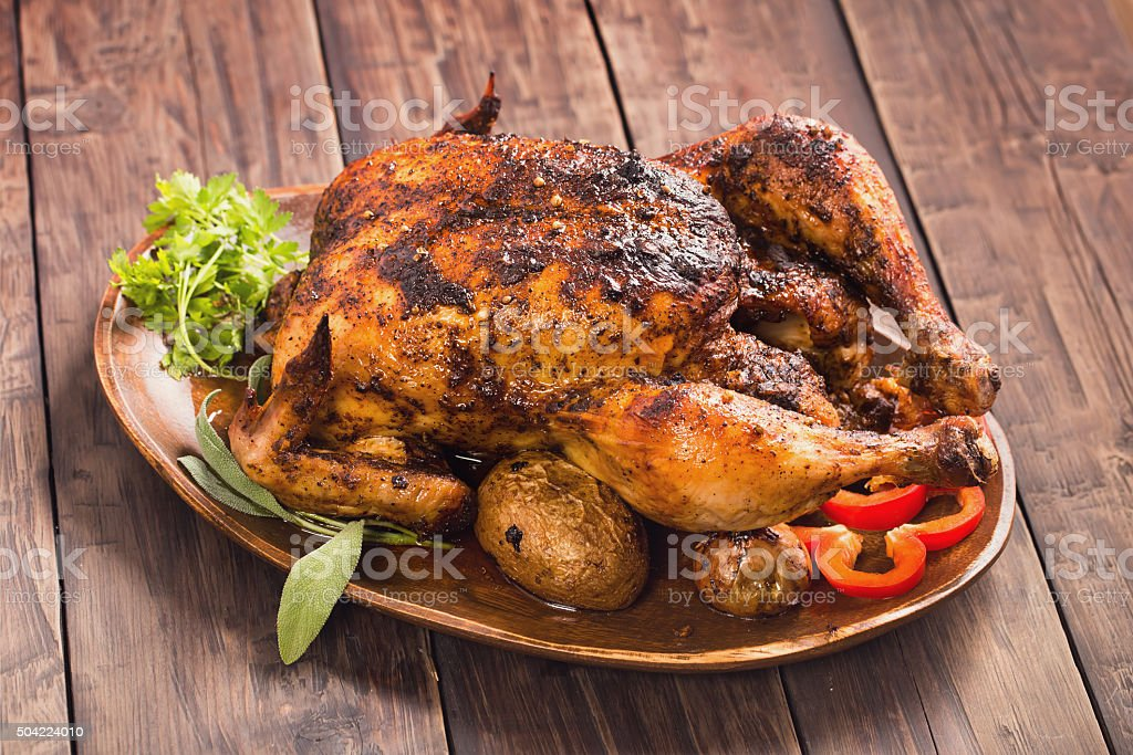 Spicy grilled chicken on wooden plate stock photo