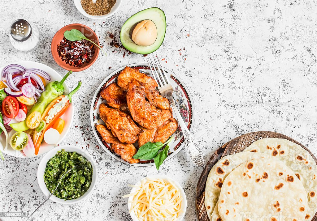 Spicy grilled chicken, tortilla, avocado, cheese, vegetables stock photo