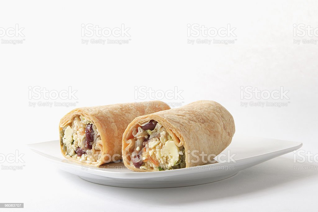 Spicy Mexican cheese and bean wrap on a white plate royalty-free stock photo