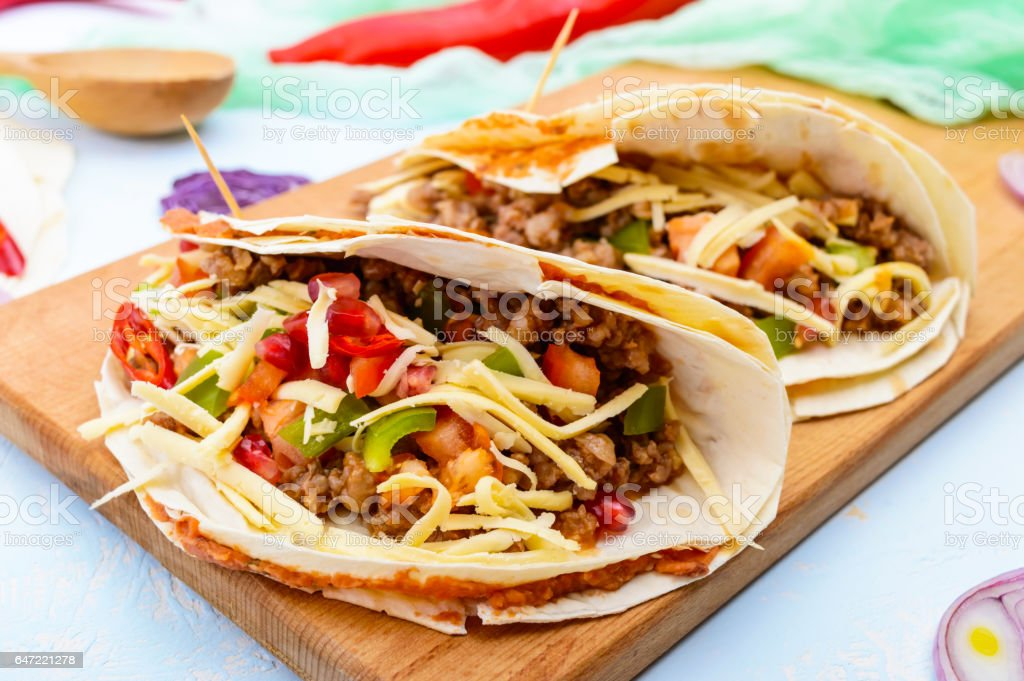 Spicy Mexican tacos with minced meat, mashed beans, vegetables, grated cheese stock photo