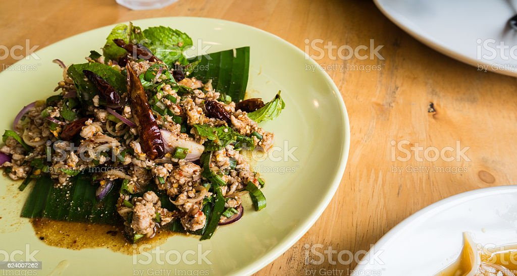 Spicy Minced Chicken Salad on wood table in restaurant. stock photo