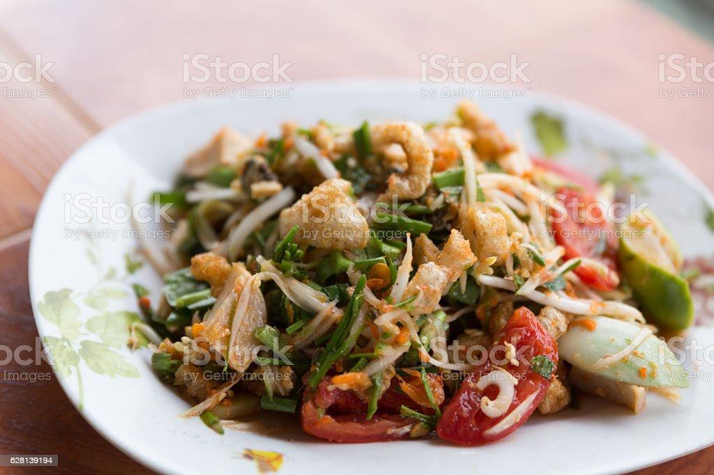spicy papaya salad with fried pork skin stock photo