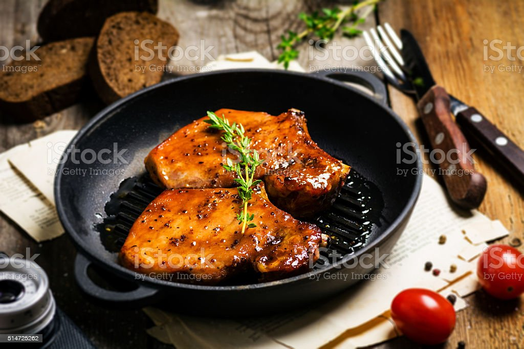 Spicy pork chops barbeque with thyme in skillet stock photo