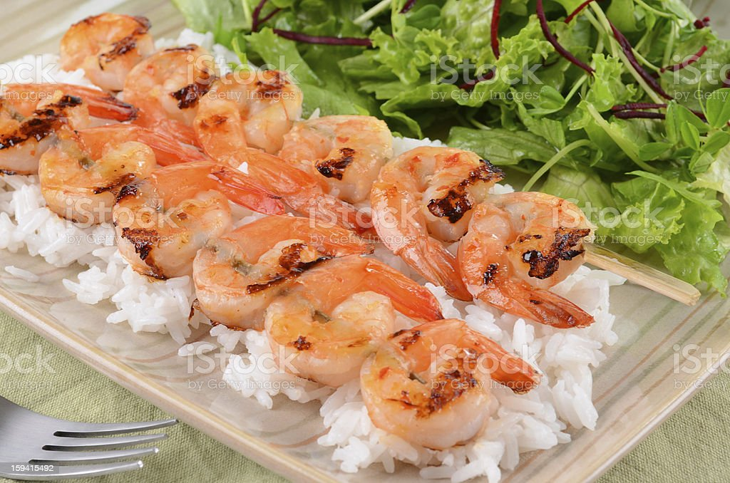 Spicy prawn skewers with rice and greens royalty-free stock photo