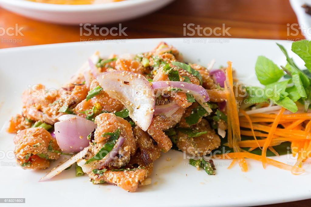 Spicy salmon salad and vegetable on white dish stock photo