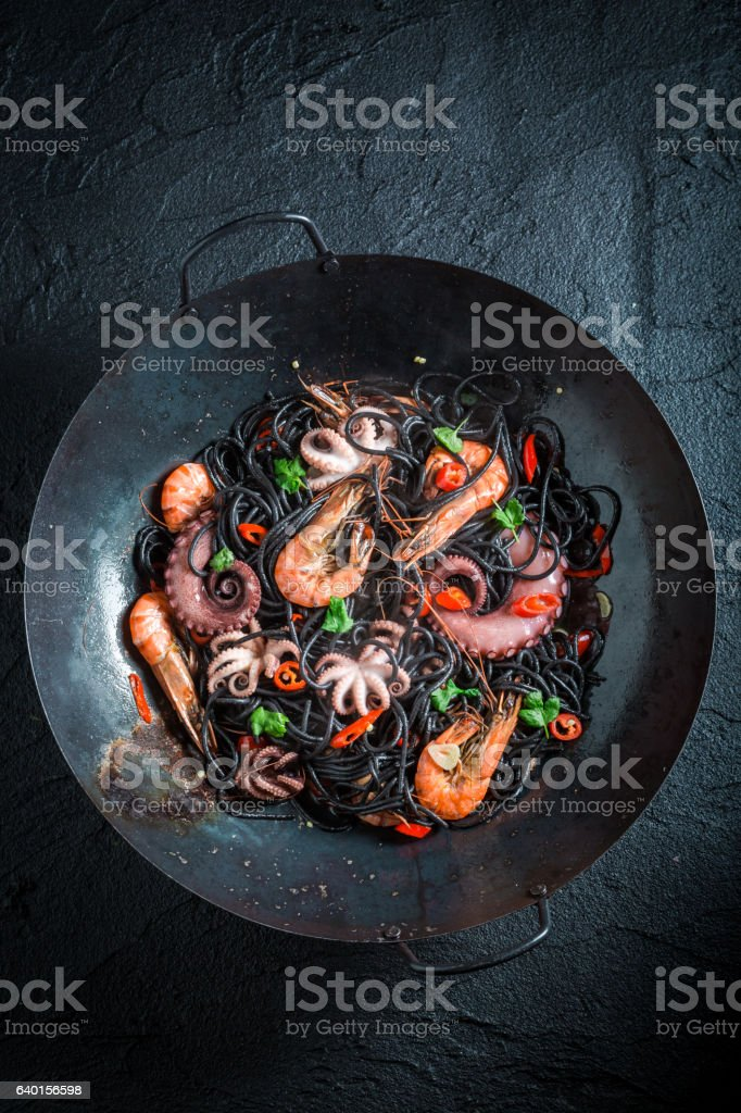 Spicy spaghetti with seafood made of octopus and tiger prawns stock photo