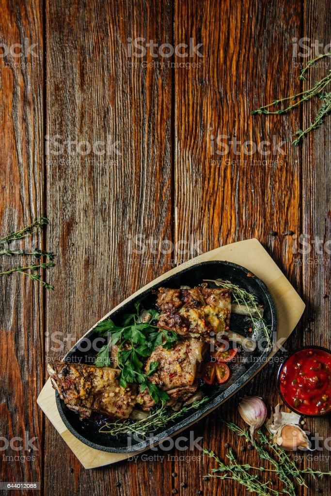 Spicy steak of the lamb chop iron pan. Food on dark wood background. stock photo