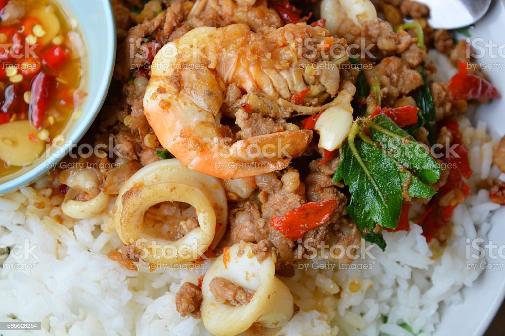 spicy stir-fried mixed seafood and chop pork with basil leaf stock photo