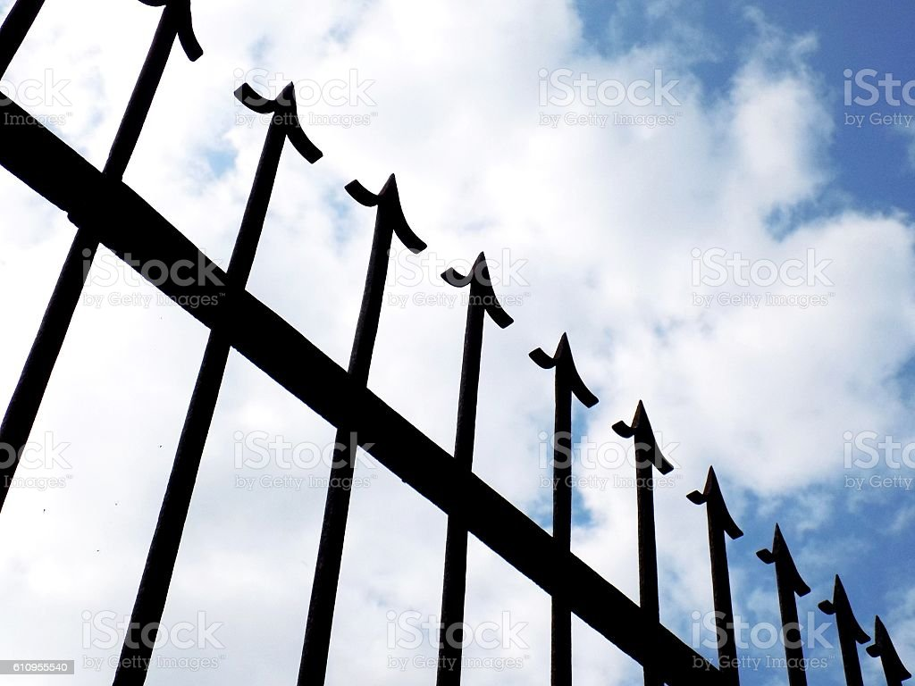 Spiky decorative iron fence and partly cloudy sky stock photo