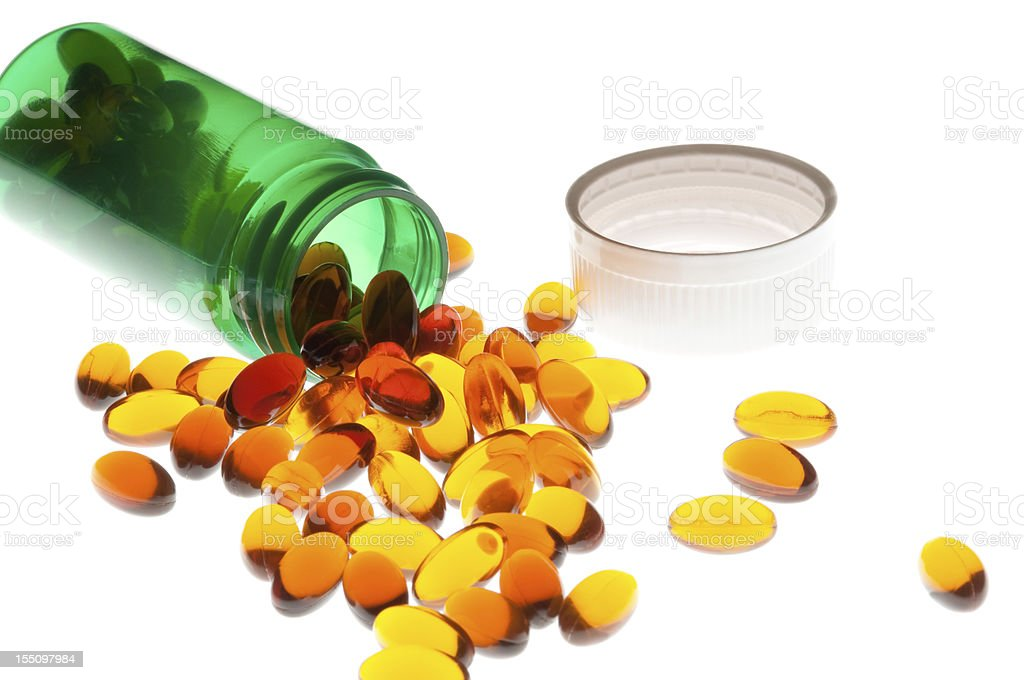 spilled amber colored vitamins stock photo