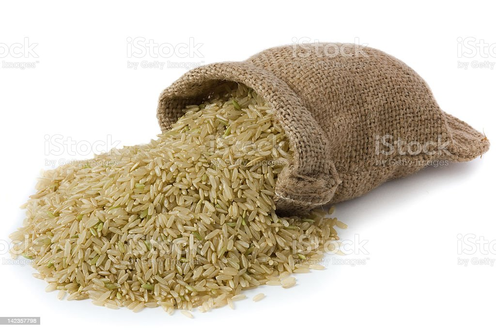 Spilled burlap bag of brown rice stock photo