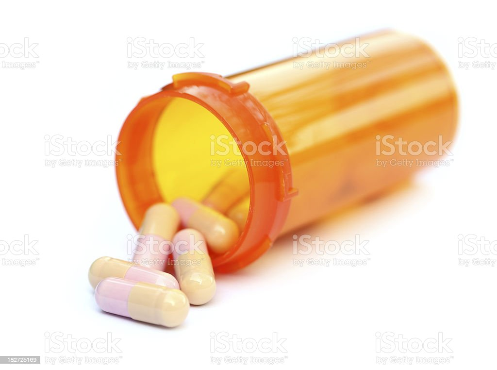 Spilled capsules from prescription bottle stock photo